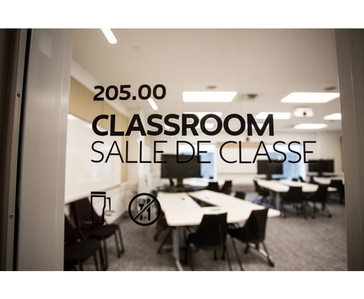 Glass door printed with black letters saying classroom/salle de classe through which you can see a TV heading a table with chairs around it