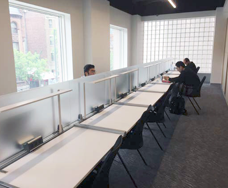 Rows of tables with individual seats separated by frosted glass partitions in a large modern study room with fluorescent lighting and chalk-patterened rug.