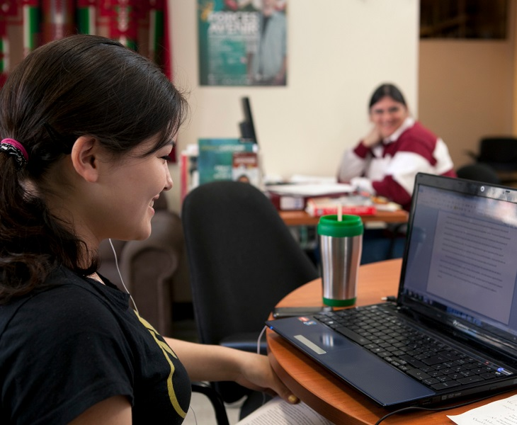 woman at laptop with ponytail smiling