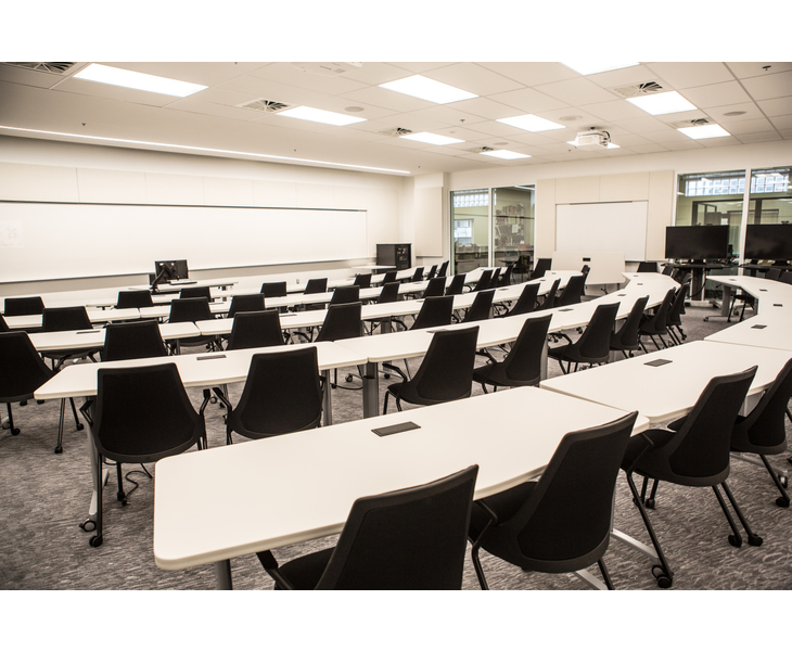 Large white-walled room with white tables and and chairs arranged in arcs facing the front of the classroom